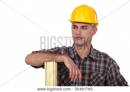 Builder stood with plank of wood