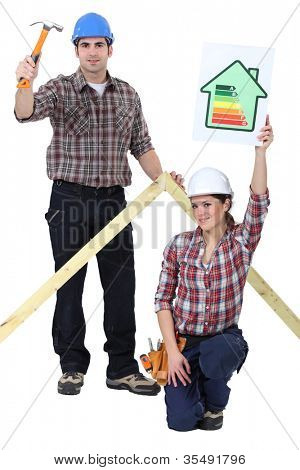 Carpenters holding a hammer and an energy efficiency rating sign