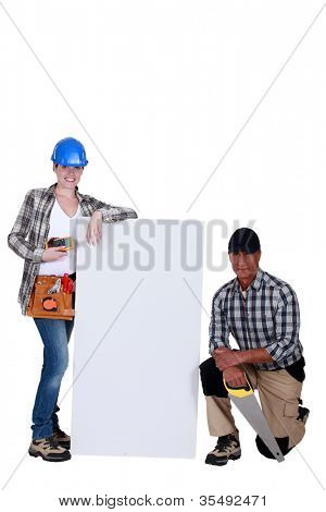 A team of tradespeople standing around a blank sign