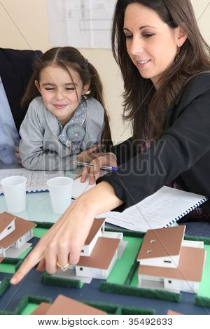 female architect in office with little girl pointing at model
