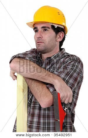 Construction worker with timber and a plane