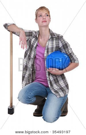 A kneeling tradeswoman holding her head up high