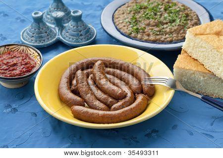 Moroccan merguez, lentil salad, bread and harissa