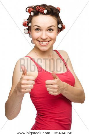 Young woman dressed in red is showing thumb up gesture using both hands while wearing hair-rollers, isolated over white