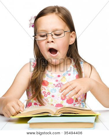 Cute little girl is yawning while reading book and wearing glasses, isolated over white