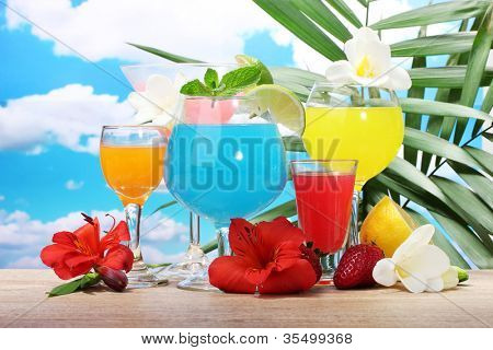exotic cocktails and flowers on table on blue sky background