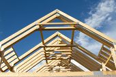 pic of rafters  - A new build roof with a wooden truss framework making an apex against a blue sky with cloud - JPG