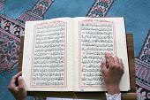 stock photo of namaz  - young muslim girl reading the Koran in mosque - JPG