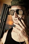 foto of cap gun  - sexy military man wearing fashionable sunglasses and cap with automatic smoking a cigar - JPG