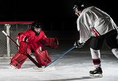 stock photo of hockey arena  - Ice hockey action shot with forward player and goalie - JPG