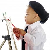 foto of french beret  - Closeup image of an adorable preschool artist painting on an easel in his smock and French beret - JPG
