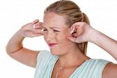 pic of noise pollution  - a young woman holds her fingers in her ears - JPG