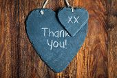 stock photo of slating  - Thank you note written in chalk on a slate heart hanging on a wooden background - JPG