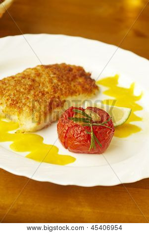 Grilled fish with orange sauce and baked tomato