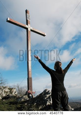Young Woman Praying Before High Cross Outdoors