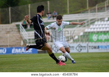 KAPOSVAR, HUNGARY - APRIL 27: Pedro Sass (in white) in actionn at a Hungarian National Championship soccer game - Kaposvar (white) vs Szombathely (black) on April 27, 2013 in Kaposvar, Hungary.