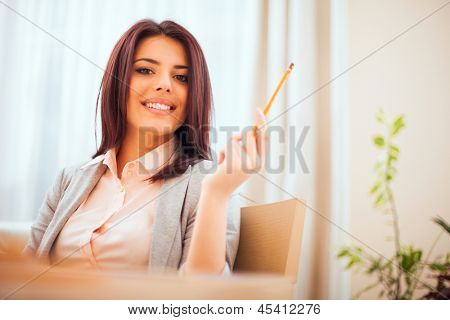Happy young woman sitting on sofa in cozy cloths
