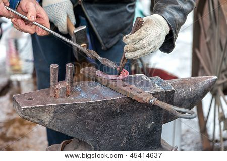 Blacksmith Forges A Hot Horseshoe On The Anvil