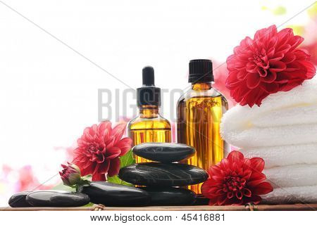 Massage oil,towel and red dahlia flower,isolated on white.