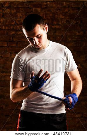 mma fighter is getting ready against brick wall