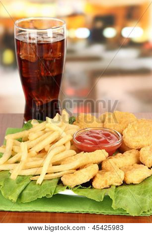 Fried chicken nuggets with french fries,cola and sauce on table in cafe