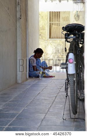 Indian Maid Having Lunch From Newsprint
