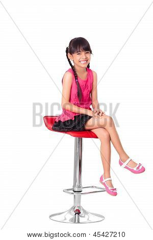 Portrait Of Happy Little Asian Girl Sitting On High Chair