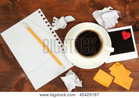 Cup of coffee on worktable covered with photo frames and stickers close up