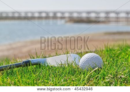 Golf Stick And Ball On Grass With A Background Of Nature. Close-up.