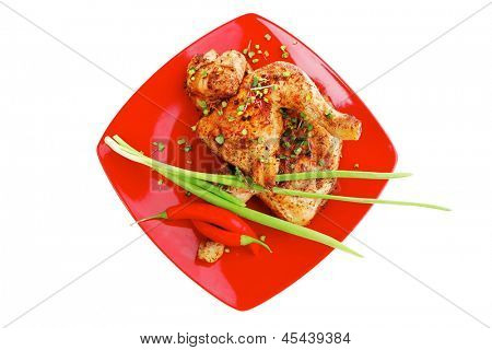 savory food : roasted chicken legs garnished with green sprouts and peppers on red plate isolated over white background