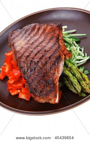 meat table : grilled beef fillet with asparagus and tomatoes served on dish isolated over white