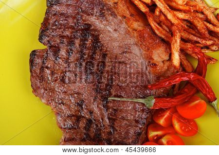 meat food : big grill beef meat steak on green square plate with dry hot chili pepper and cherry tomato isolated on white background