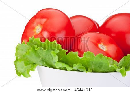 Close-up Fresh Tomatoes With Green Salad Leaf In Bowl Isolated On White Background