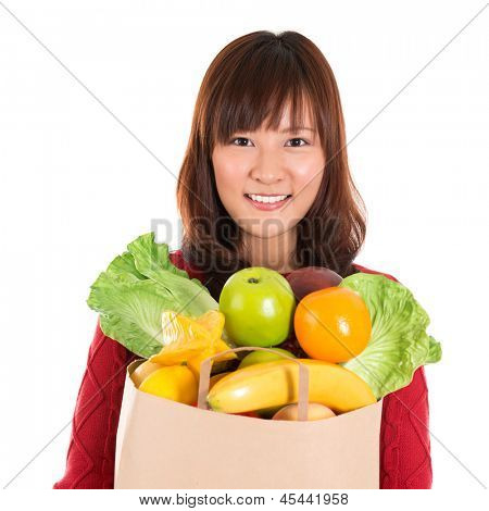 Happy grocery shopper. Smiling young Asian woman holding paper shopping bag full of groceries isolated on white.