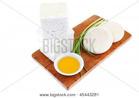 dairy product : raw soft mediterranean feta white cheese cubes and round on wooden plate isolated over white background