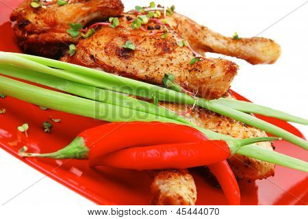 roast meat : chicken legs garnished with green sprouts and peppers on red plate isolated over white background