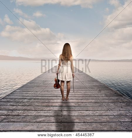 young woman with violin on a wharf