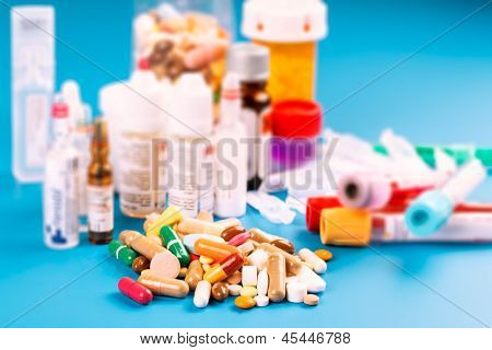 Medications tablets and capsules in a beaker