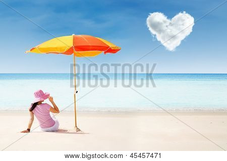Asian Tourist At Beach Under Umbrella And Love Cloud