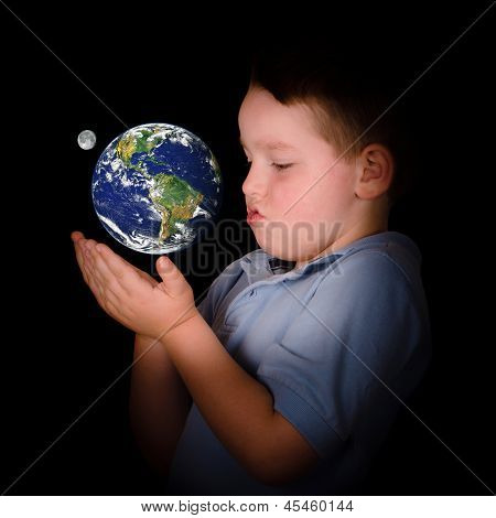 Fascinated child studying the Earth between his hands in education or environment concept