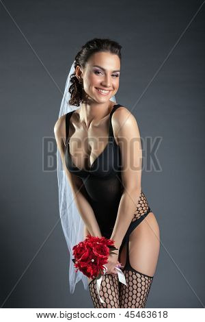 Laughing model posing in black lingerie and veil