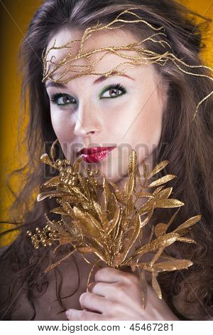 Portrait Of Beautiful Gilr With A Gold Branch In Hair