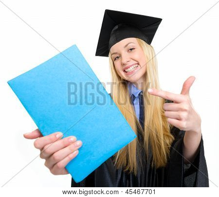 Smiling Young Woman In Graduation Gown Pointing On Book