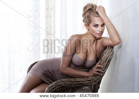 Gorgeous Blonde Girl Posing On Wicker Chair, Looking At Camera.