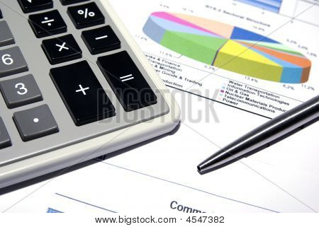 Calculator And Steel Pen On Printed Financial Data.