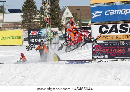 Red And Black Polaris Snowmobile Soaring Over Jump