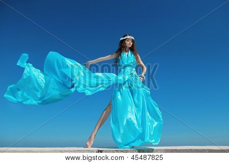 Fashion Model Woman With Blowing Dress Over Blue Sky, Outdoors