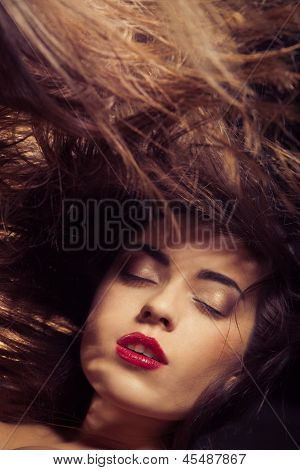 Young woman with red lips and flowing hair