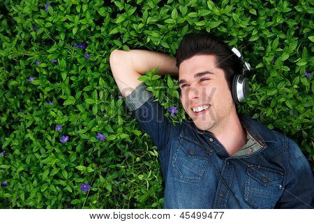 Happy Young Man Lying On Grass, Listening To Music