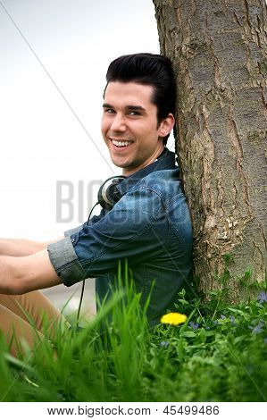 Happy Young Man Sitting In Nature
